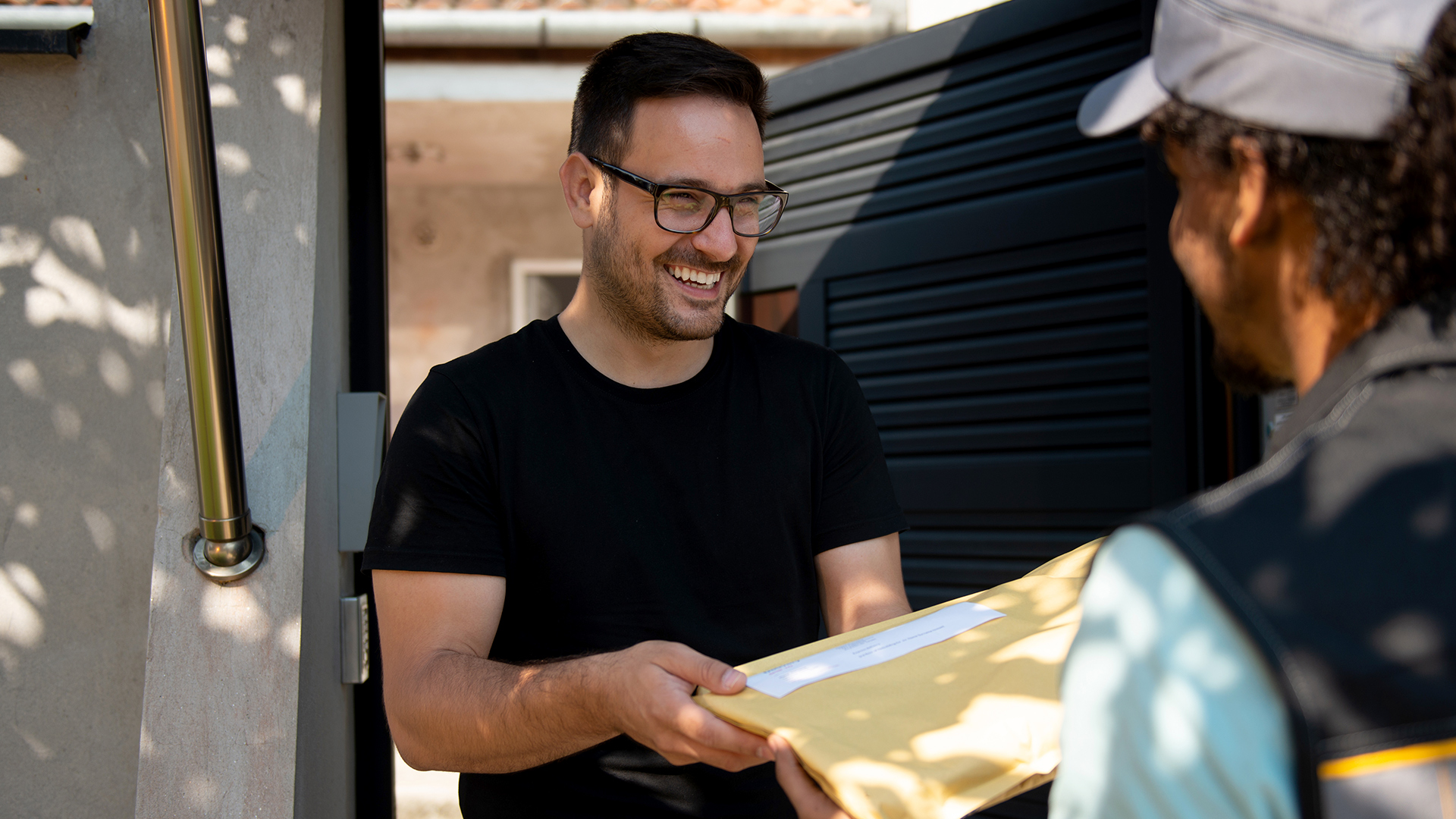 deliveryman giving a parcel a happy customer