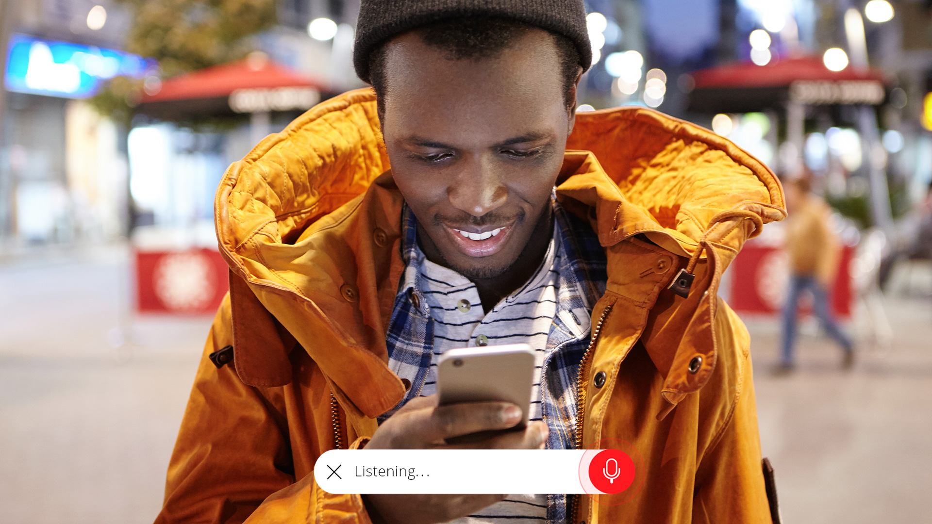 man smiling at phone using voice interface