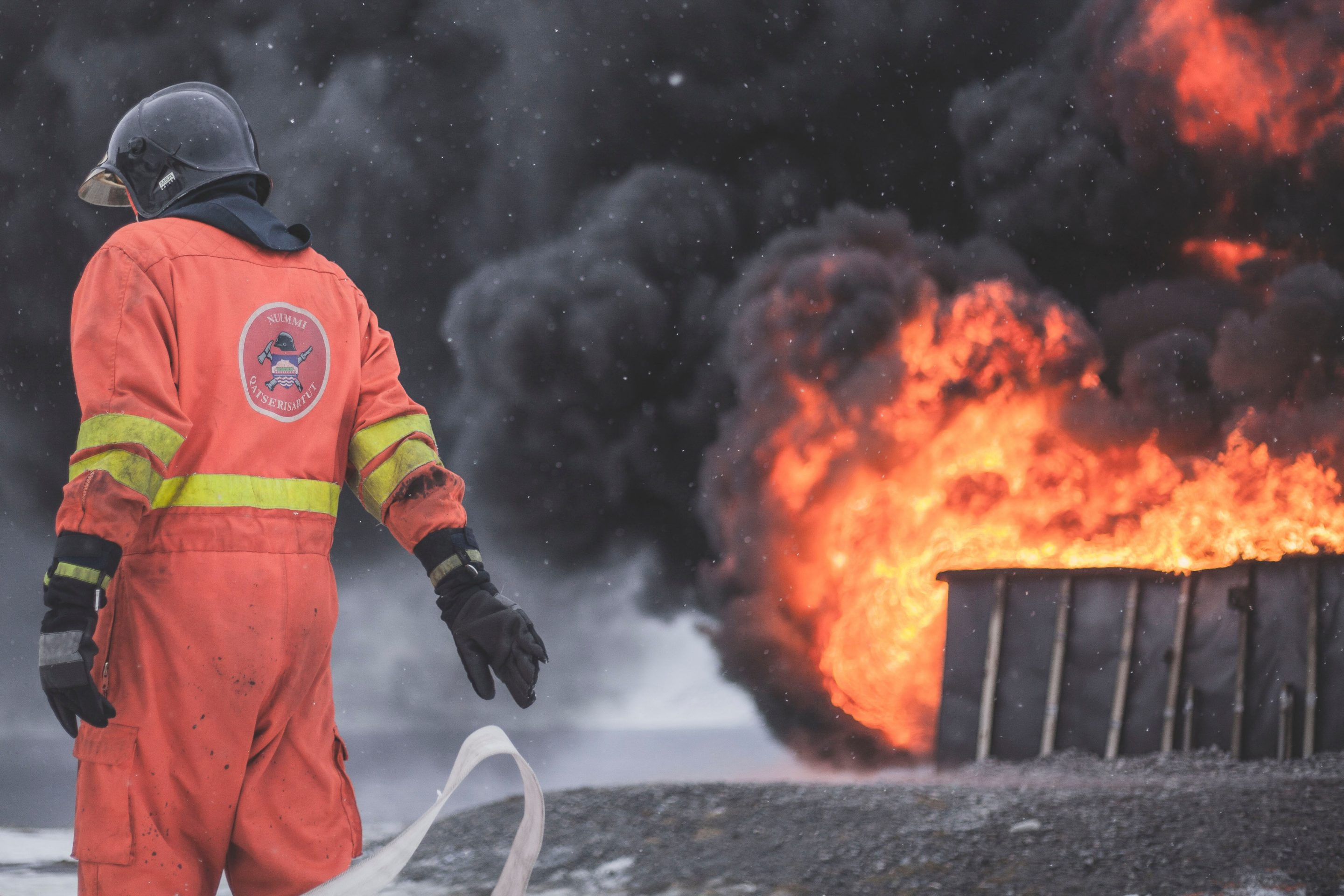 man in safety suit with blazing fire in the background