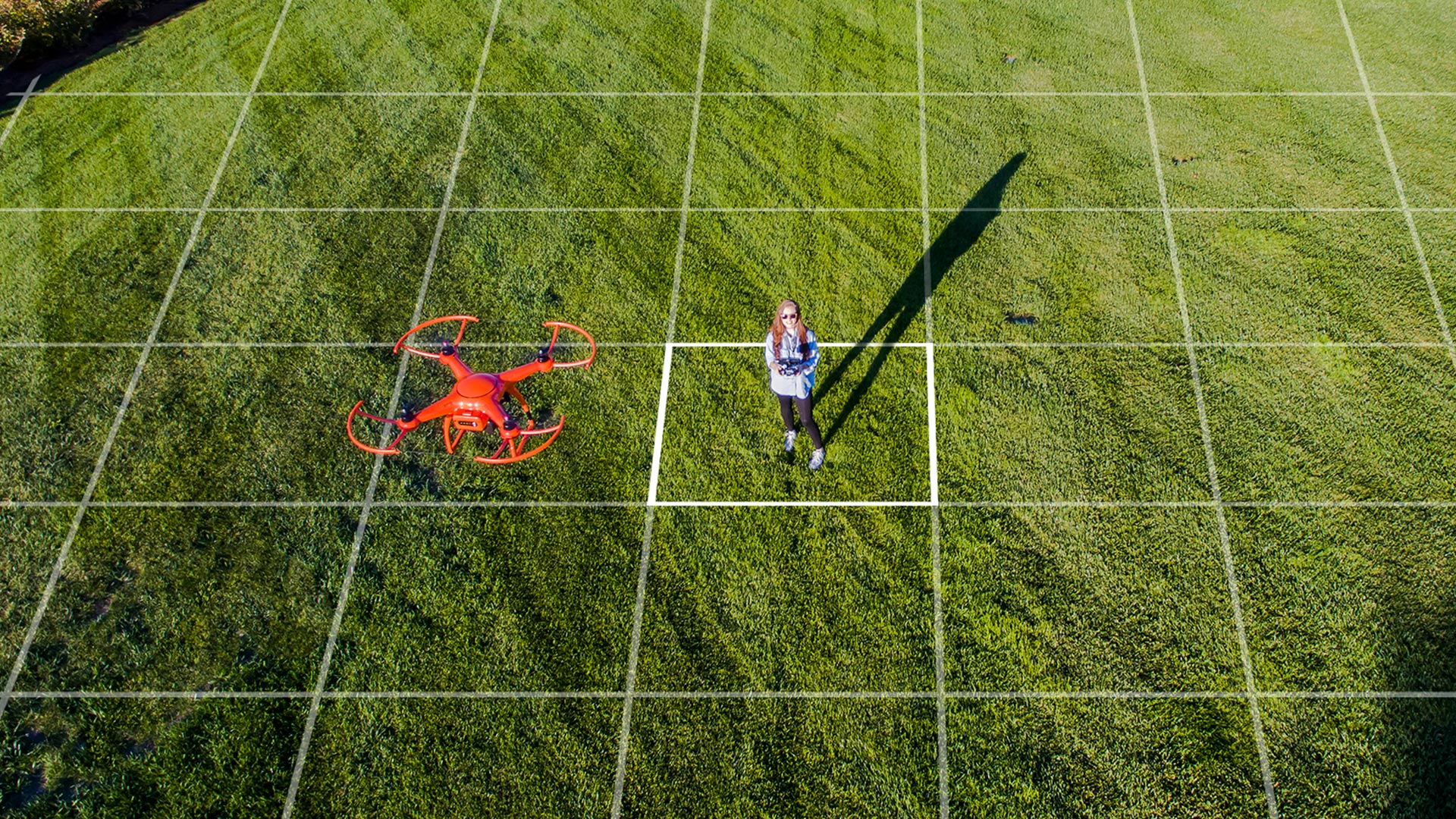 woman operating a drone in a field