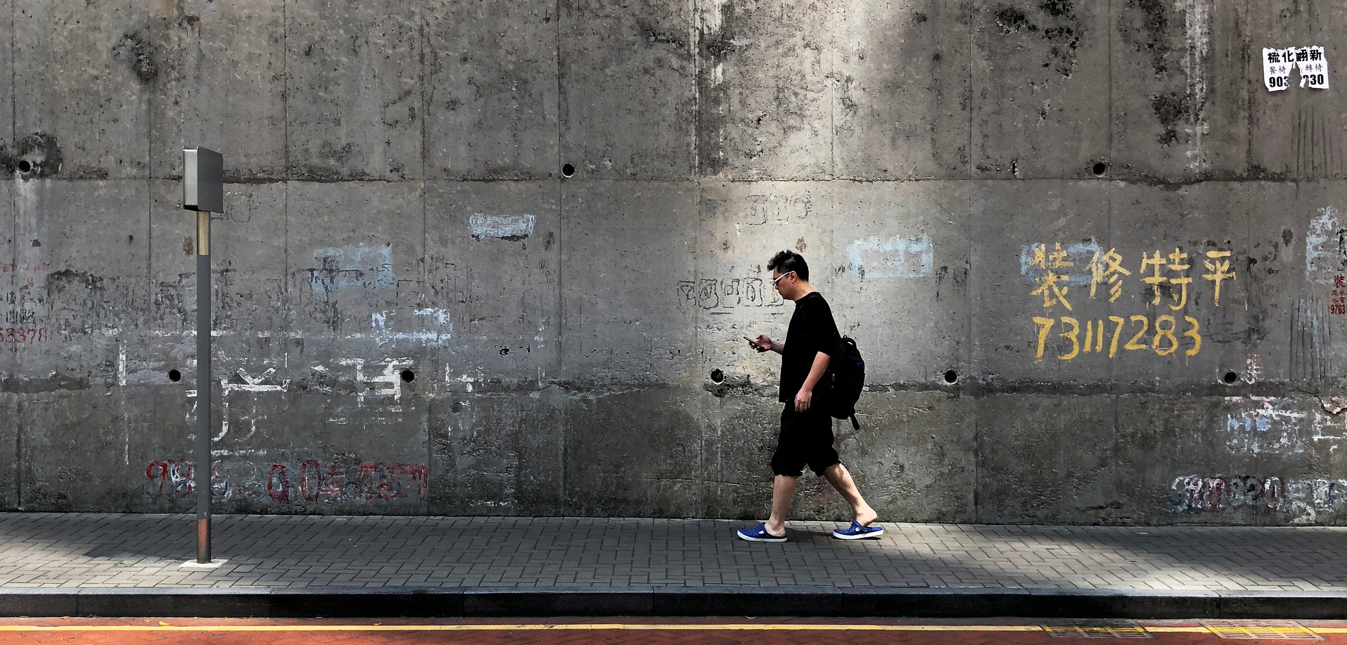 man walking on pavement using phone