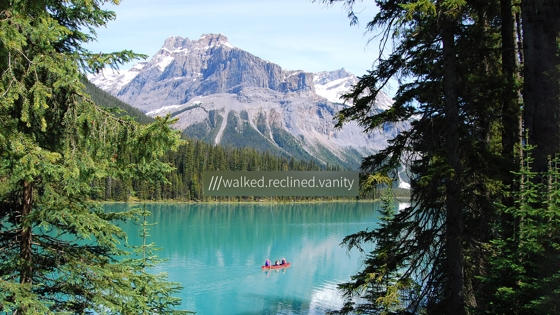 tourists row in a blue lake surrounded by forest and mountains