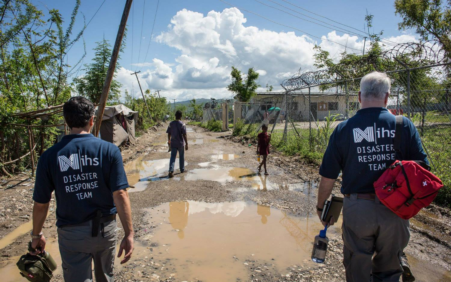disaster response team walking through muddy puddles