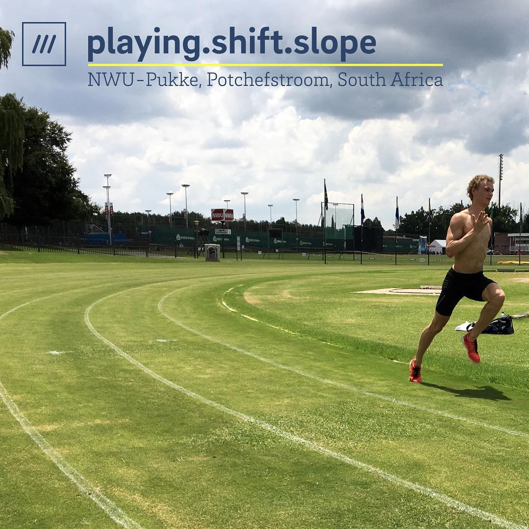 man running around a sports track at 3 word address playing.shift.slope