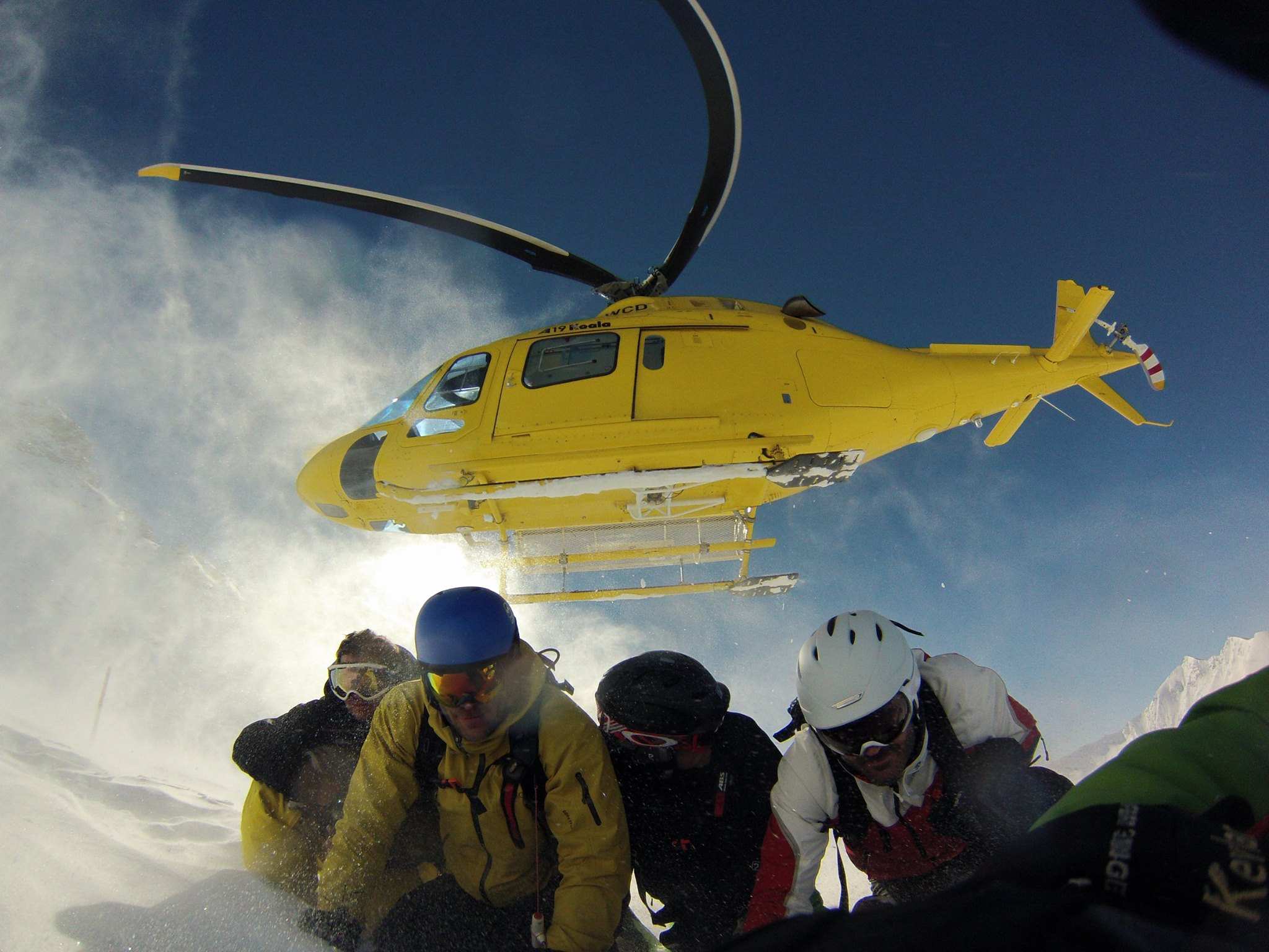 skiers duck as helicopter tires to land in snowy conditions
