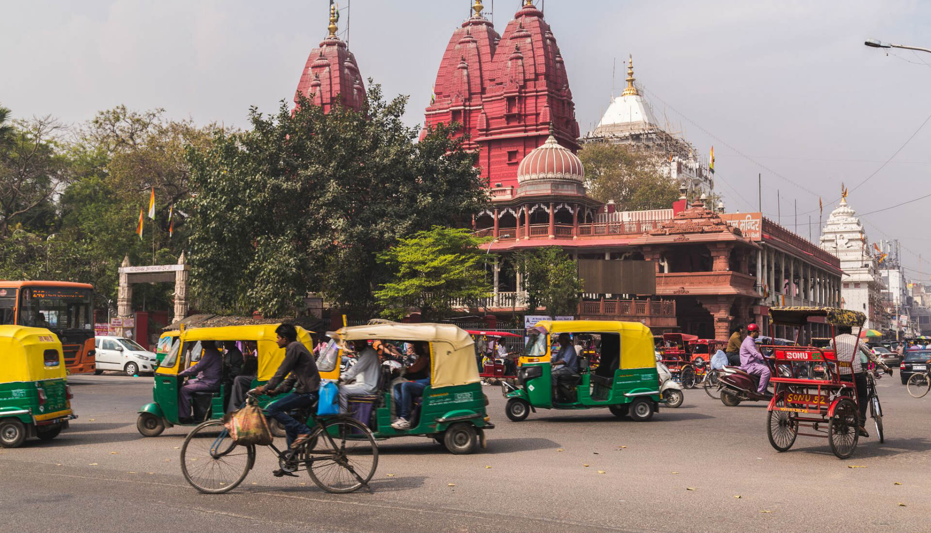 tuk tuks driving on roads with temples in background