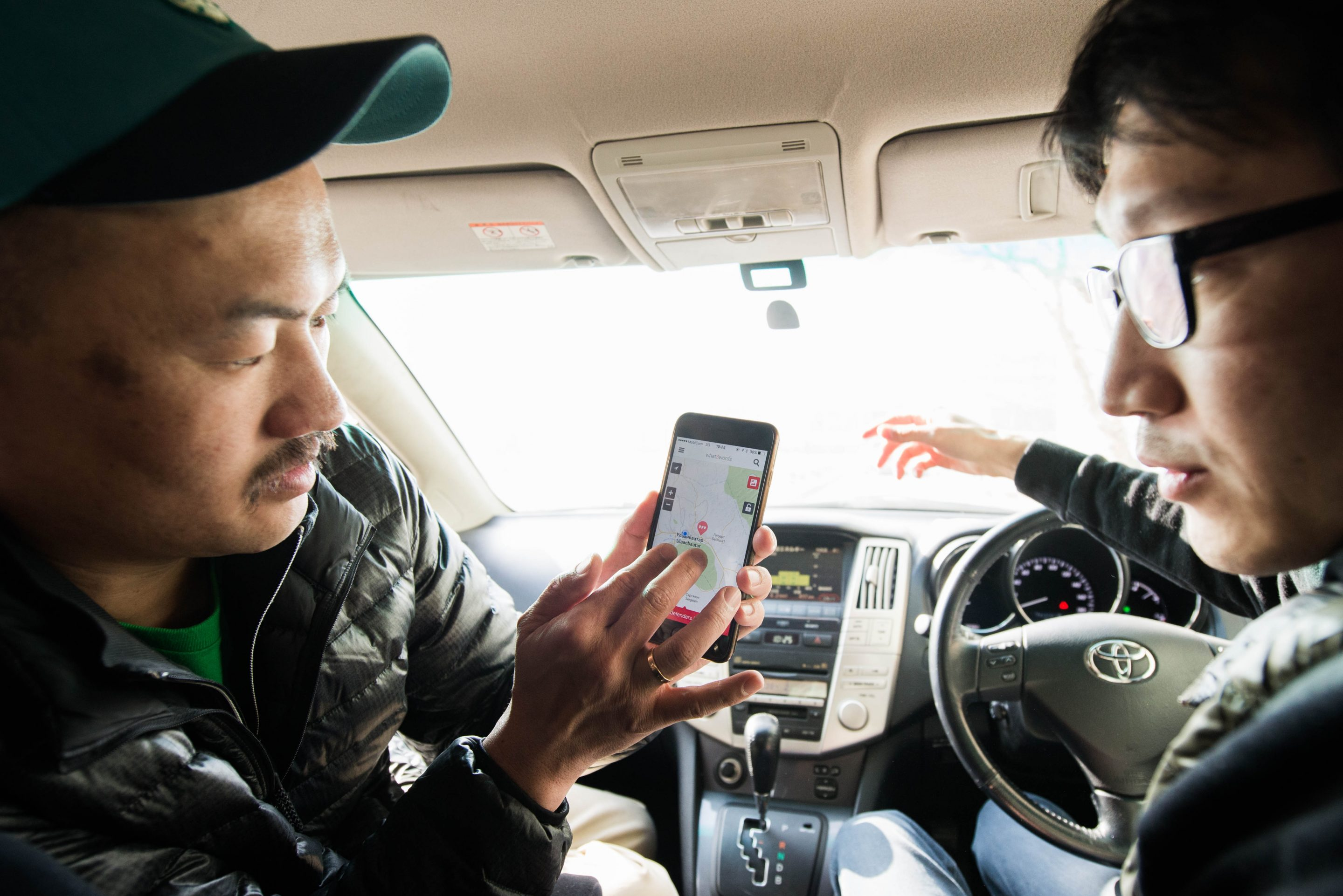 two men look at what 3 words app in car