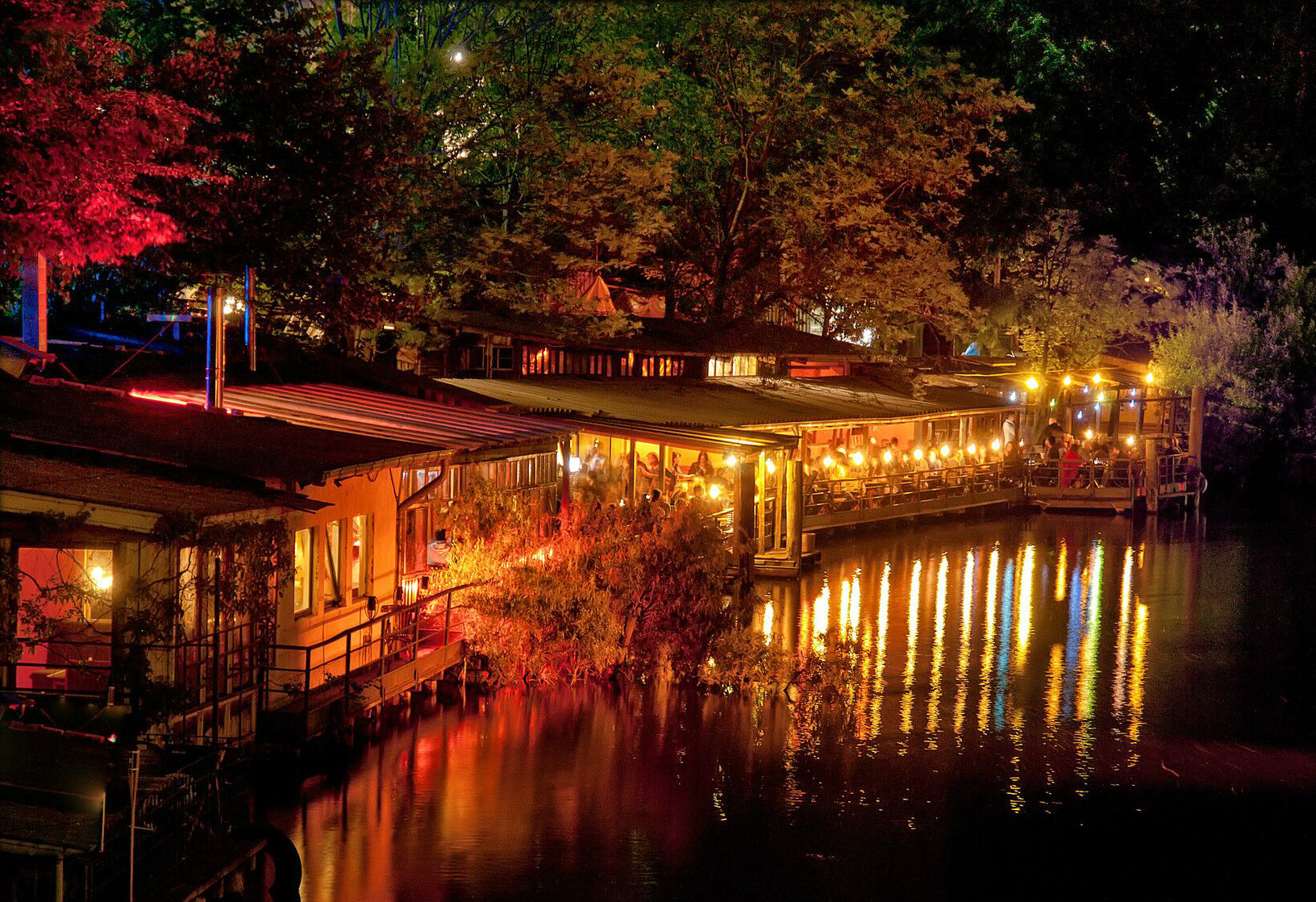 restaurants by riverside lit up at night