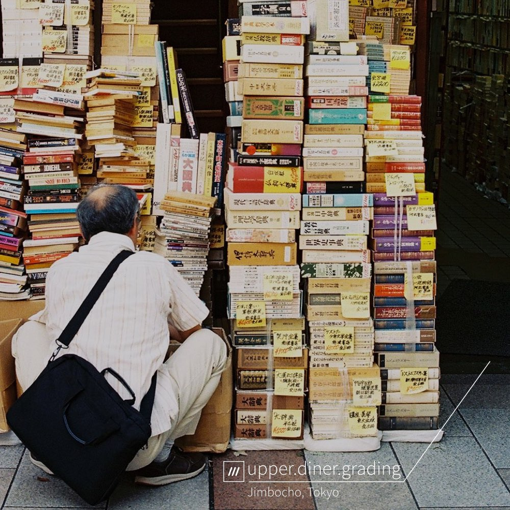 man crouches down next to pile of books at 3 word address upper.diner.grading