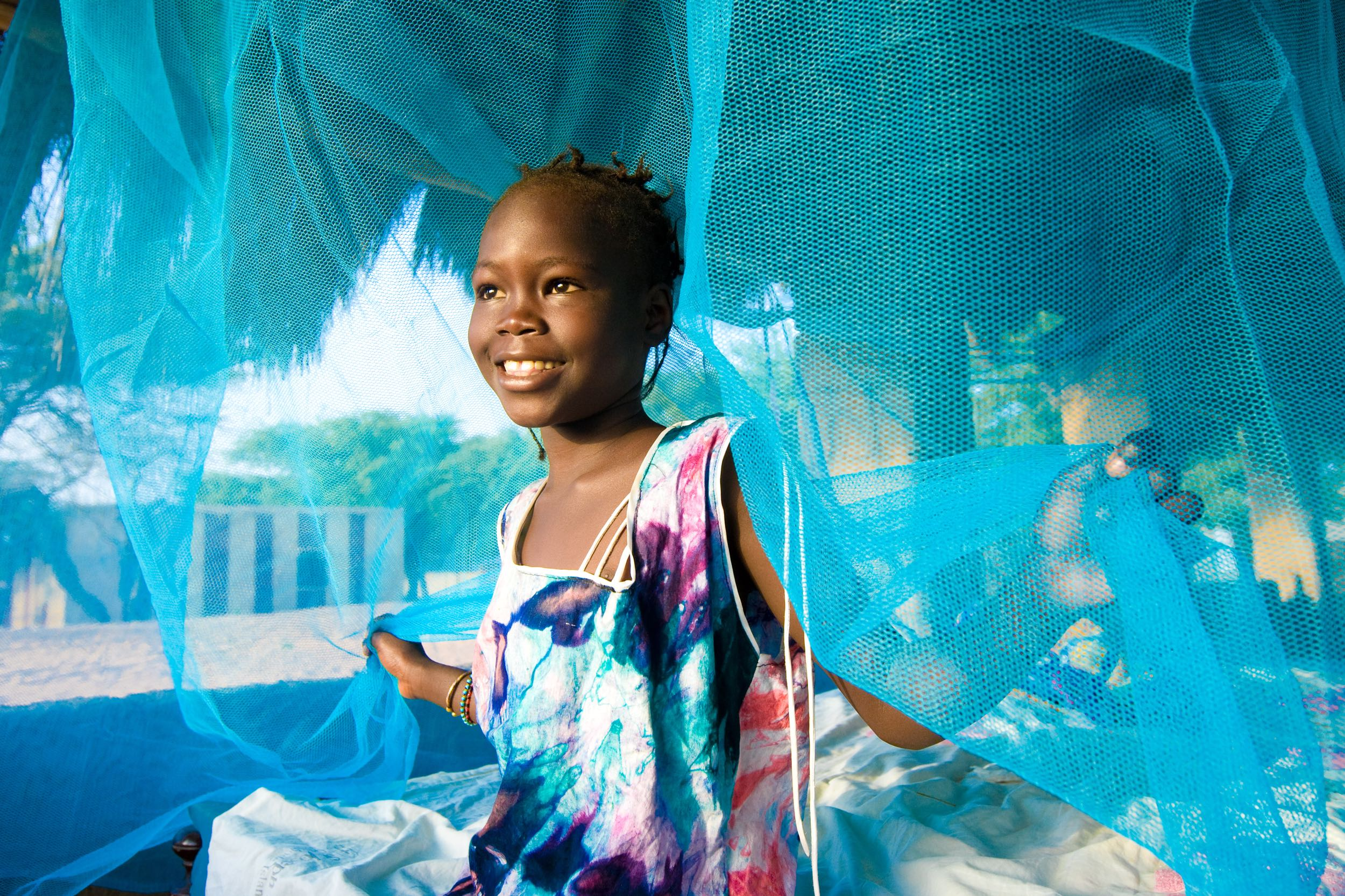 girl lifting up blue netting curtains