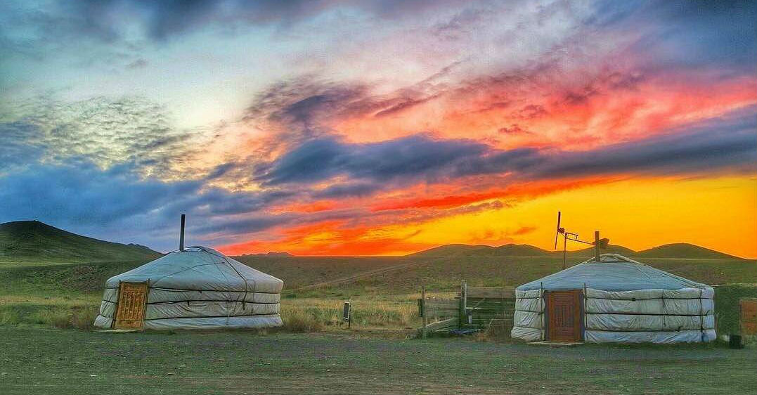 tents with an orange sky and sunset behind them in a field