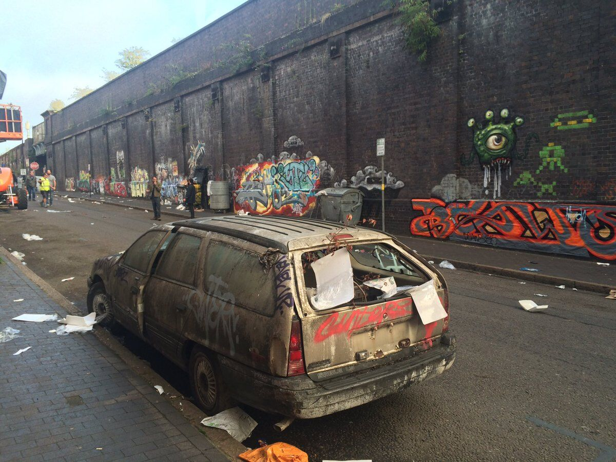 litter on the road with walls spray painted and broken dirty car