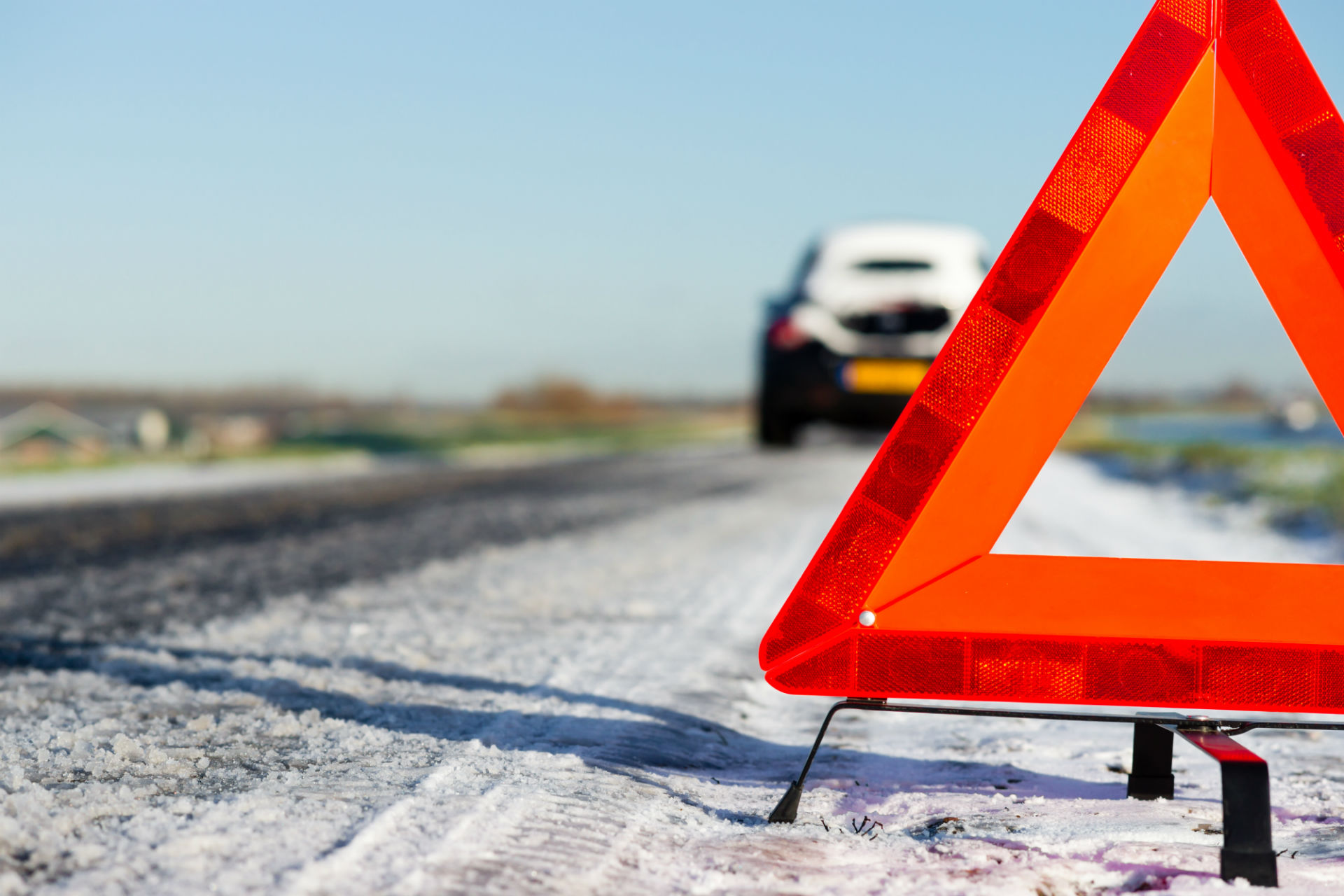 snowy road with warning triangle placed further behind a car