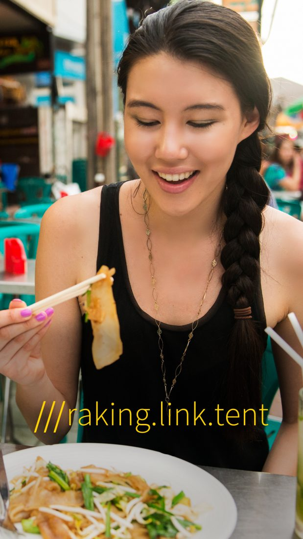 woman eating Thailand street food at 3 word location raking.link.tent