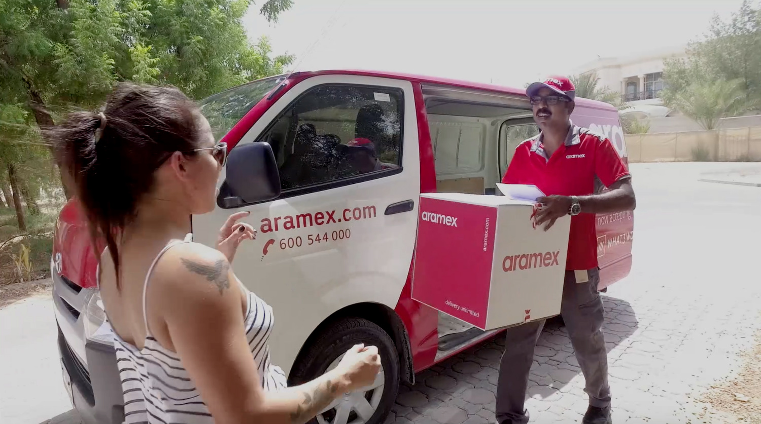 delivery man handing woman parcel