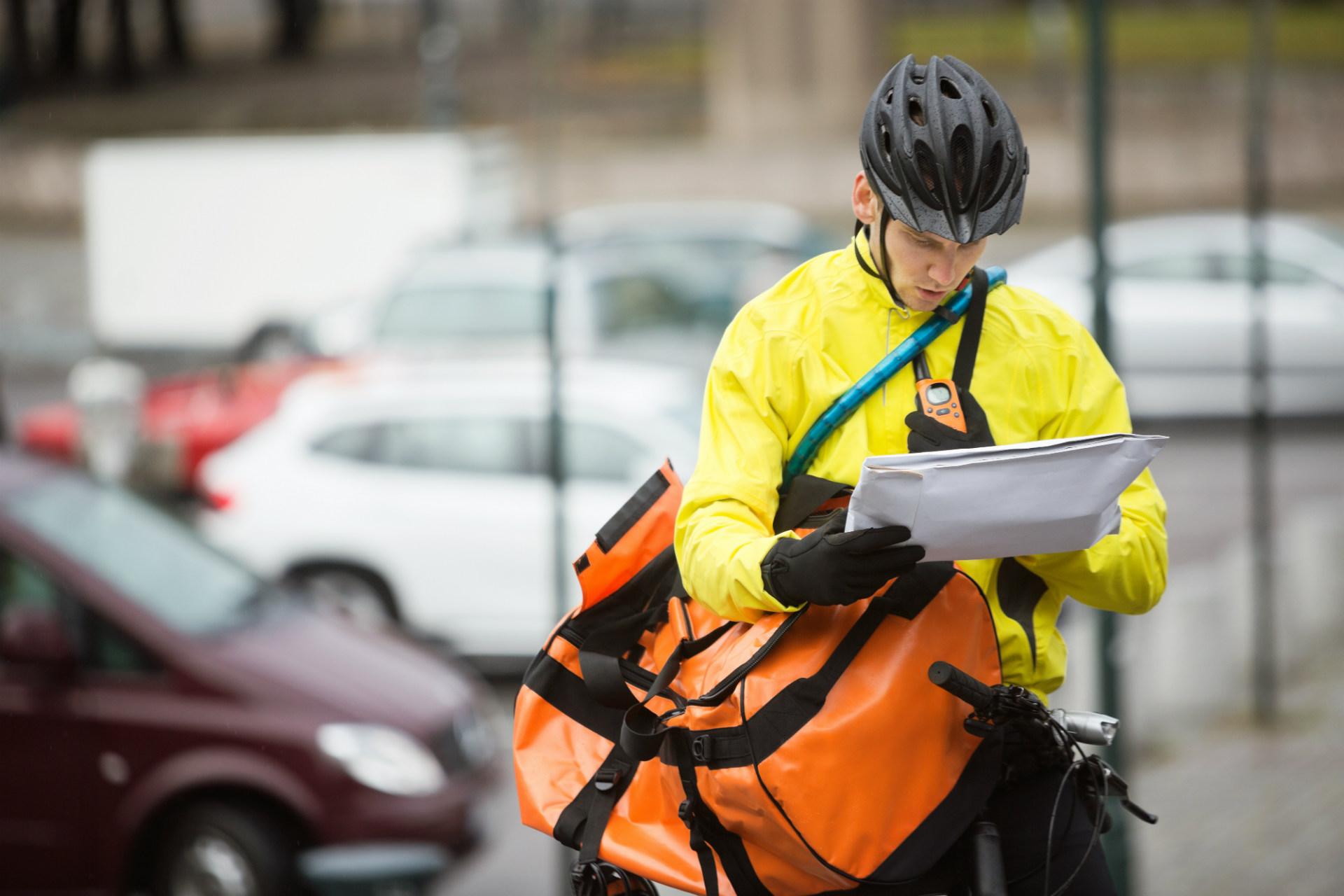 deliveryman on bike looking at parcel