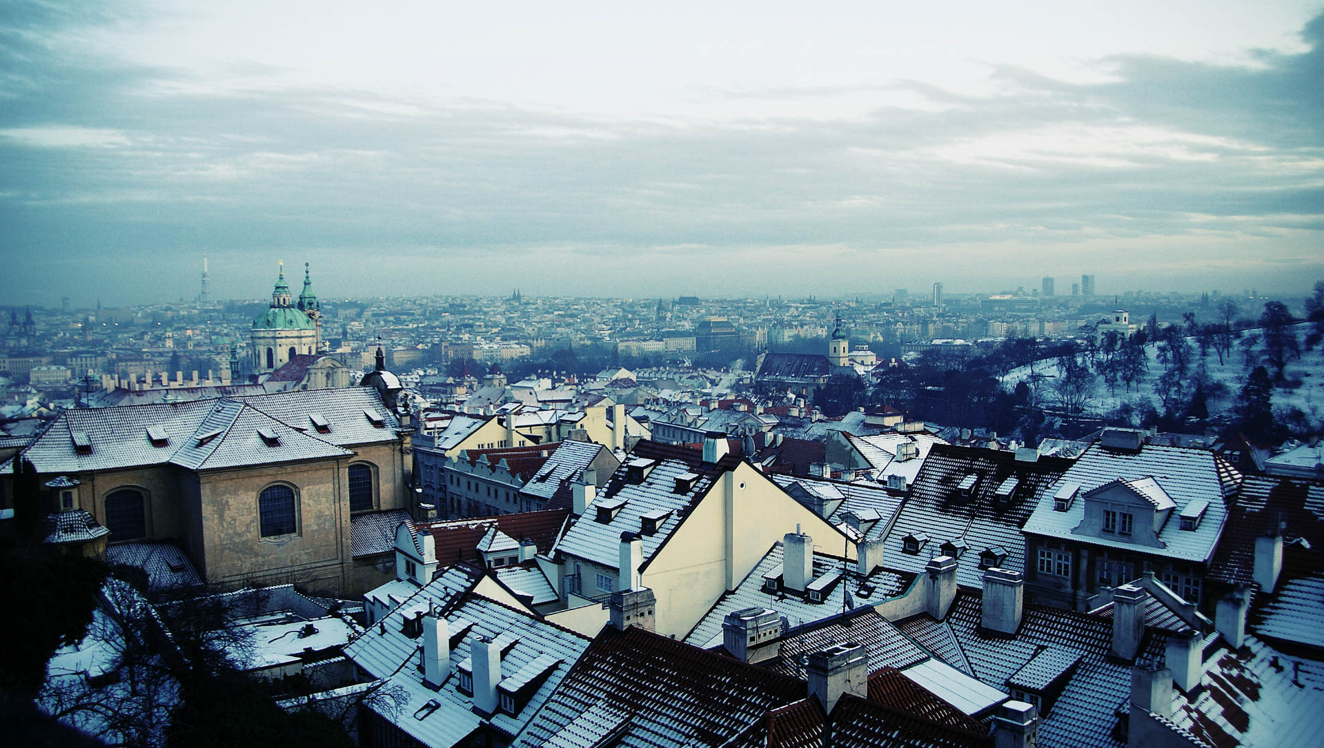 view of city rooftops on a snowy day