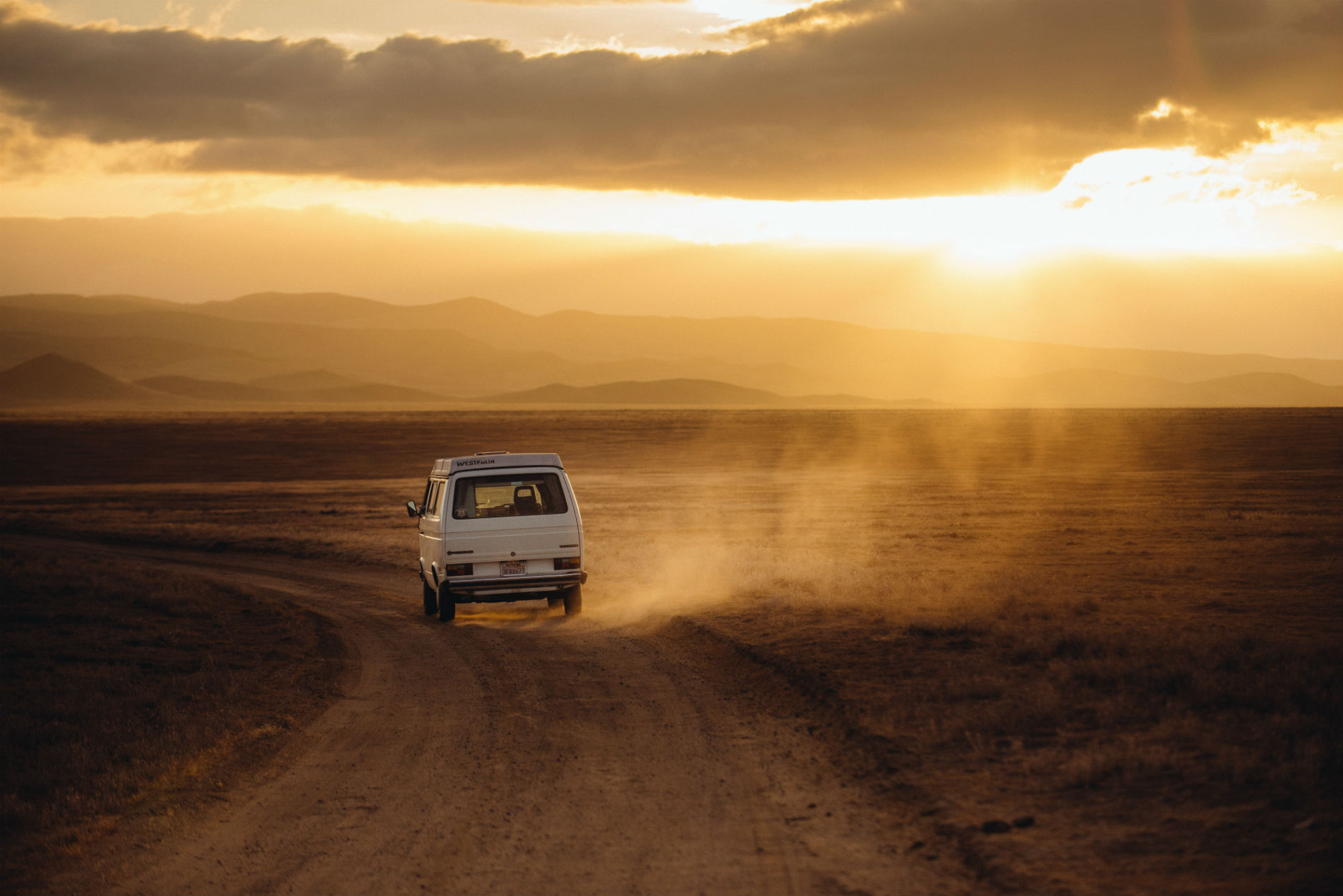 car drives through dusty baron road