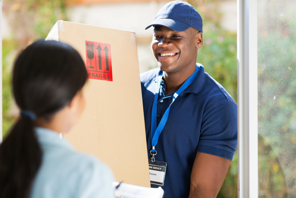 delivery man giving woman fragile box