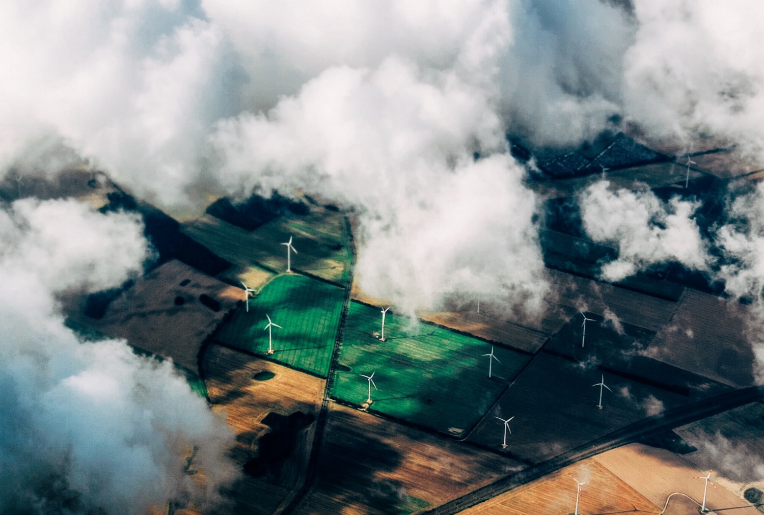 view of fields and wind turbines with some clouds covering the area