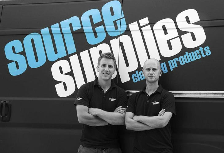 two men pose in front of company cleaning van