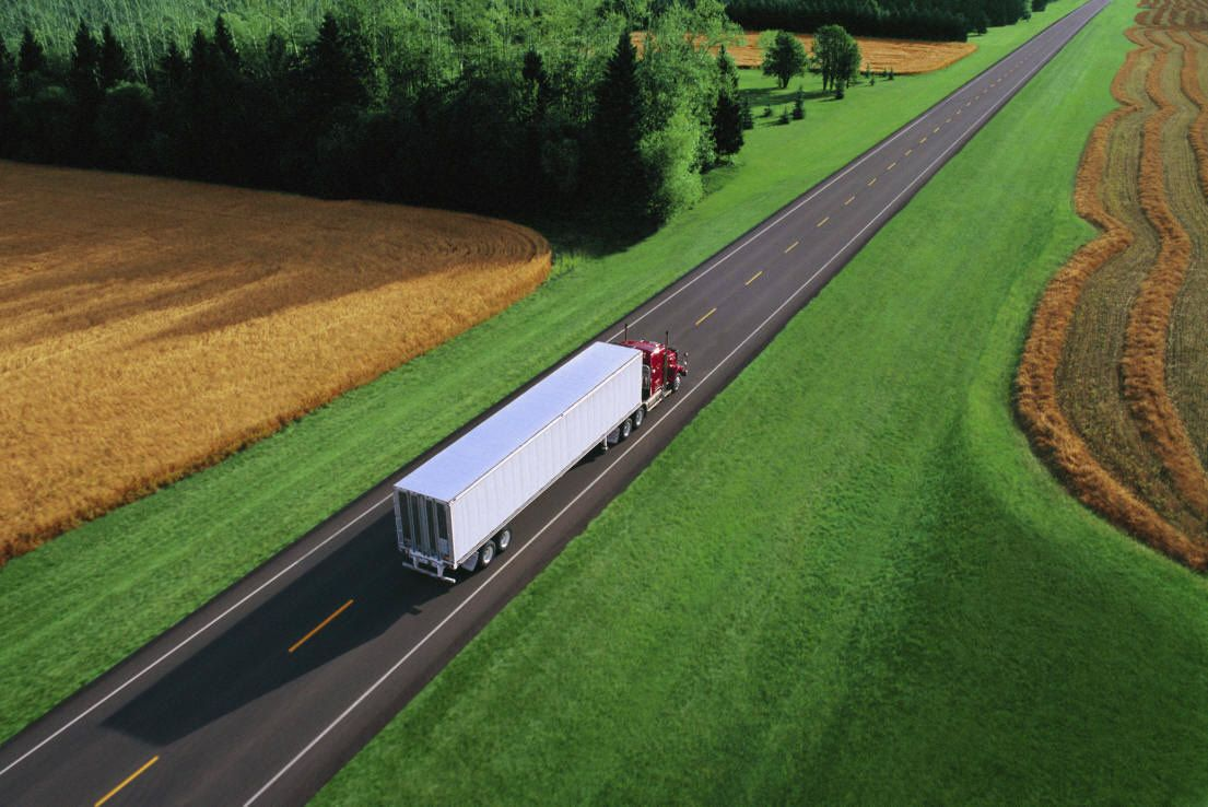 lorry driving on straight road with fields either side