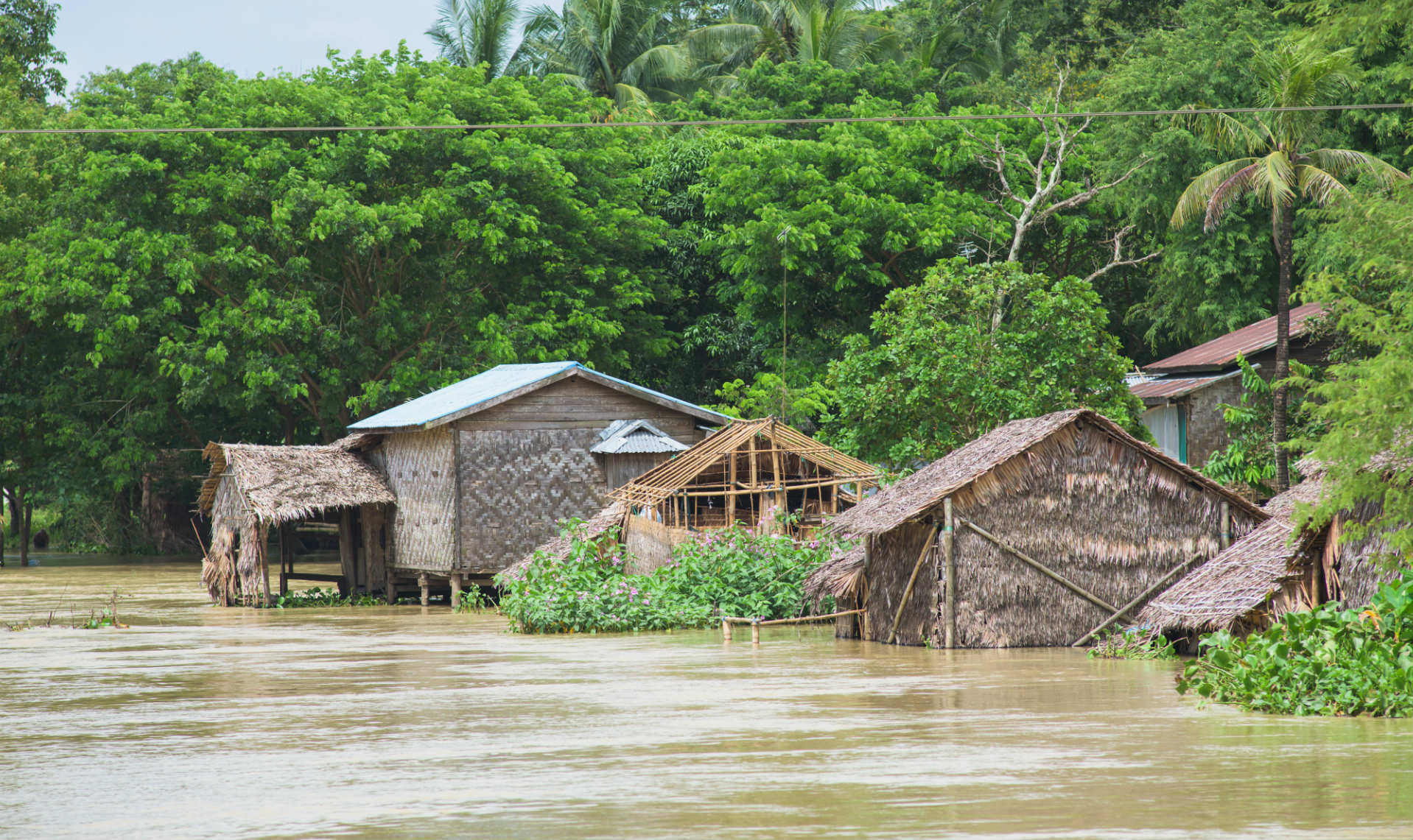 wooden made houses surrounded by flooded waters