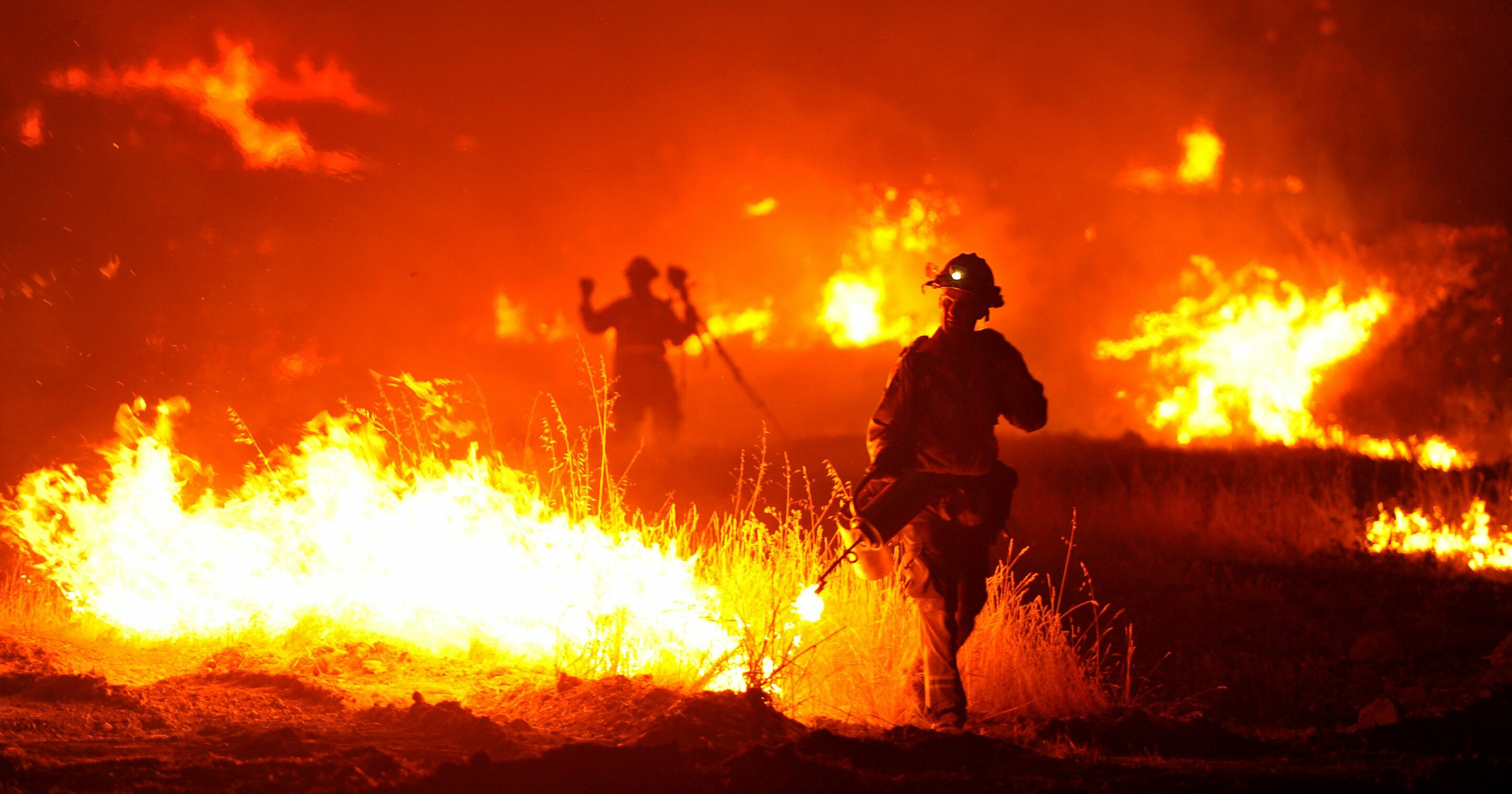 firefighters fighting a blazing fire in a field