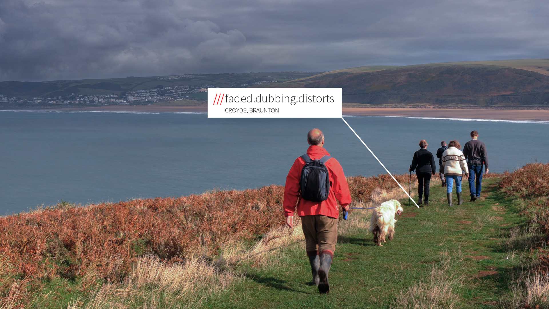 people walking dog on grassy path with sea in background at 3 word address faded.dubbing.distorts