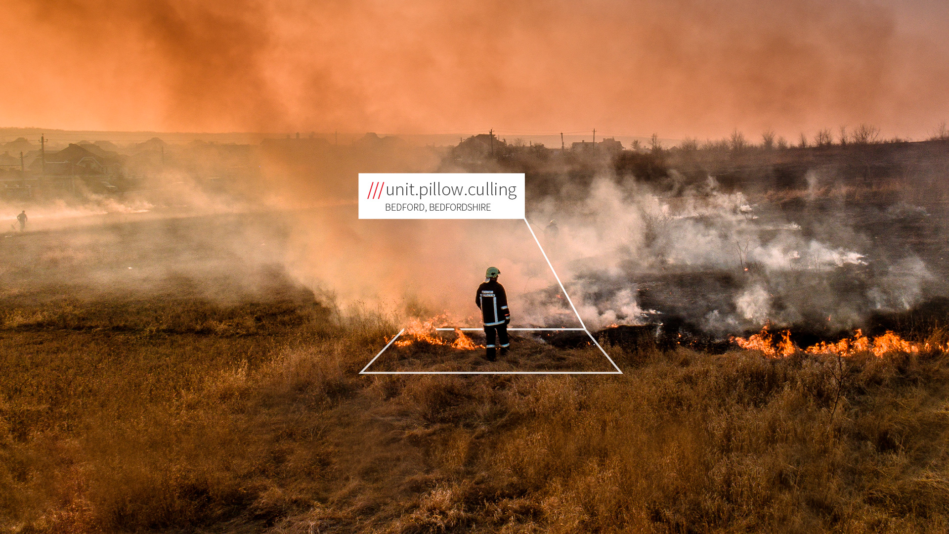 A fire burning through fields with a firefighter in 3 word location unit.pillow.culling
