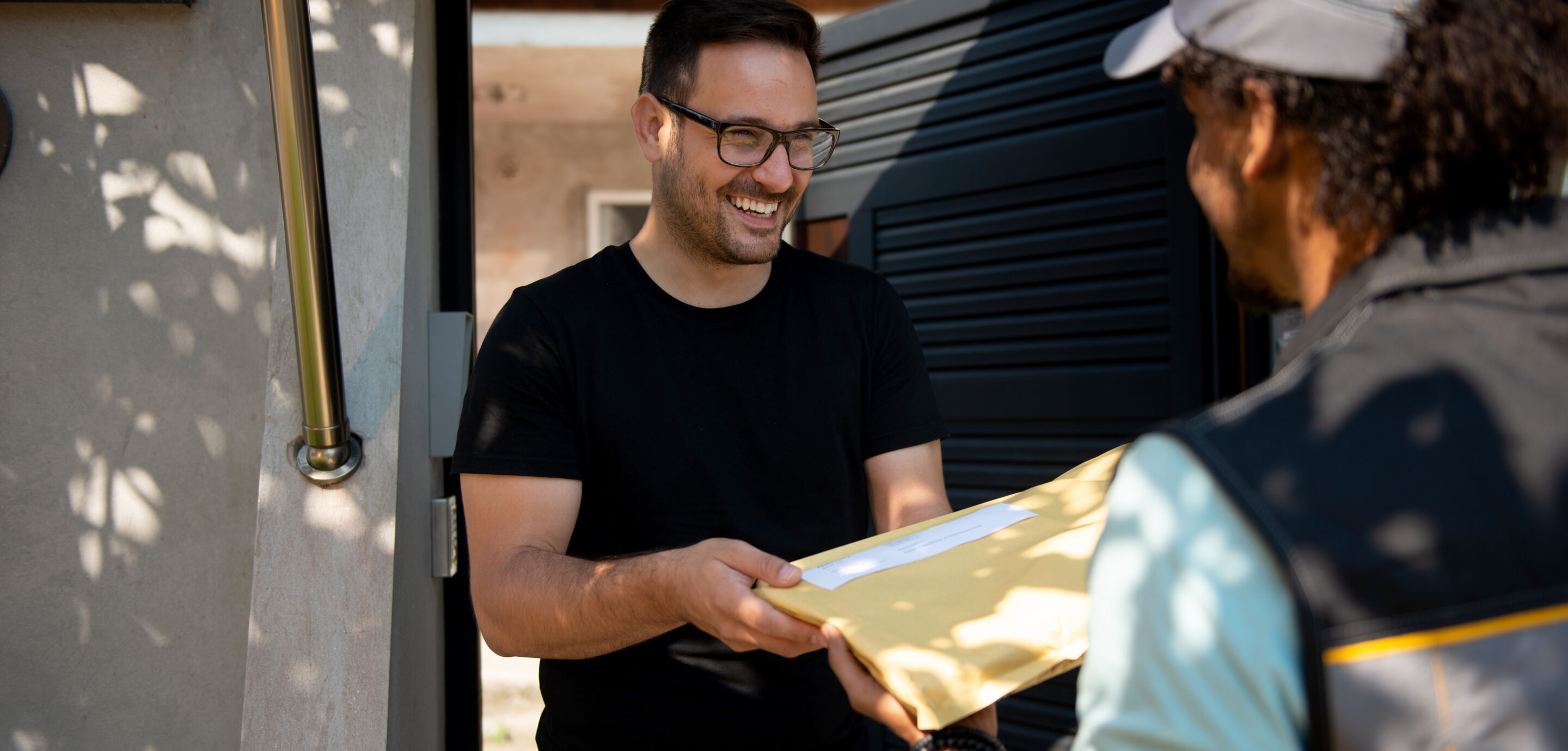 A man receiving a parcel from the mailman