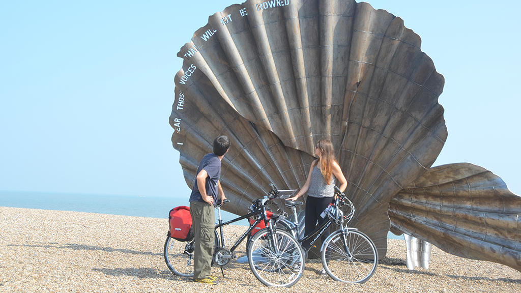 2 cyclists on a beach looking at a shell statue