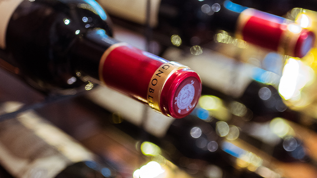 A close up of a red wine bottle in a cellar