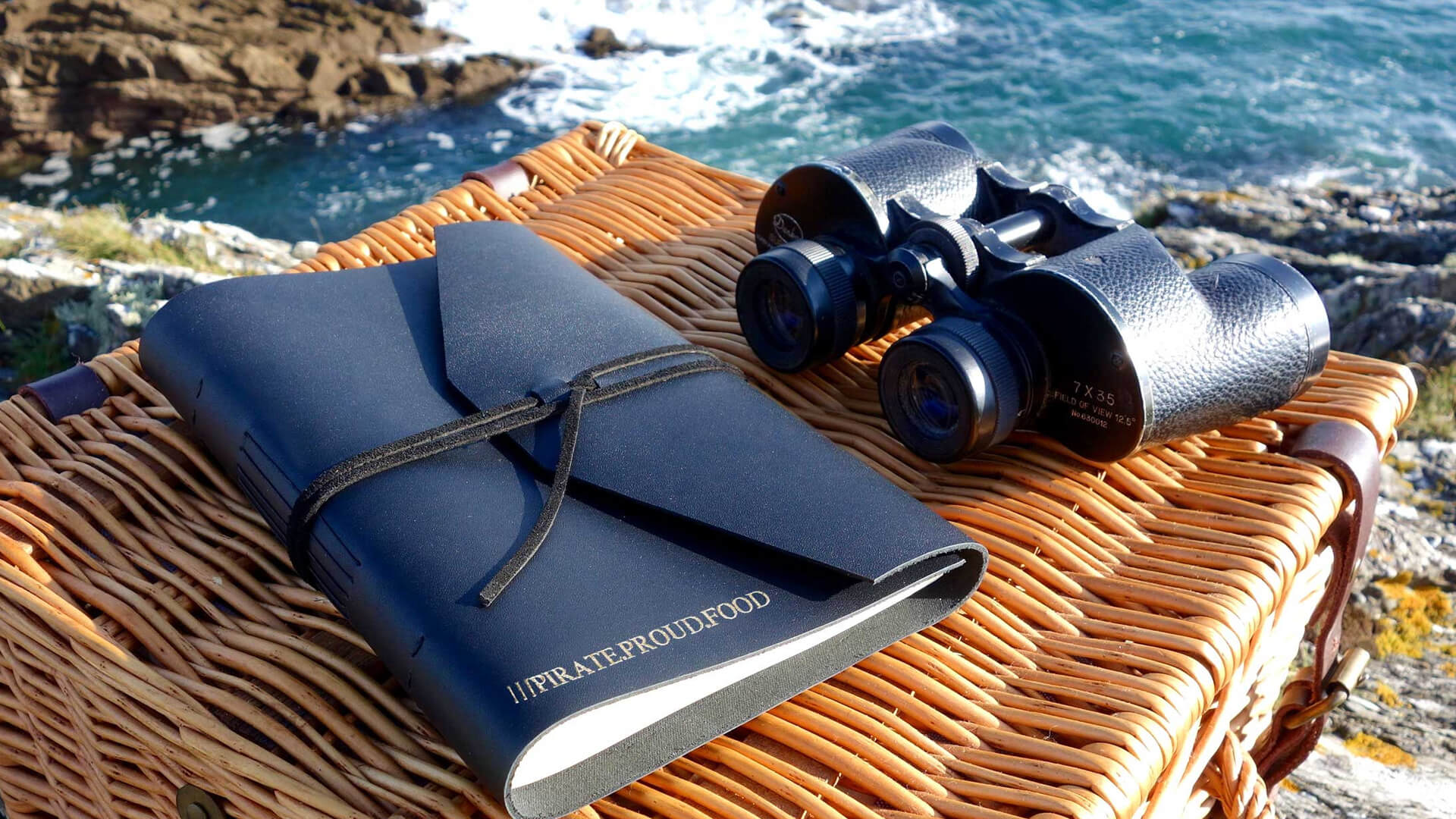 Binoculars and travel diary on top of basket with the sea in background