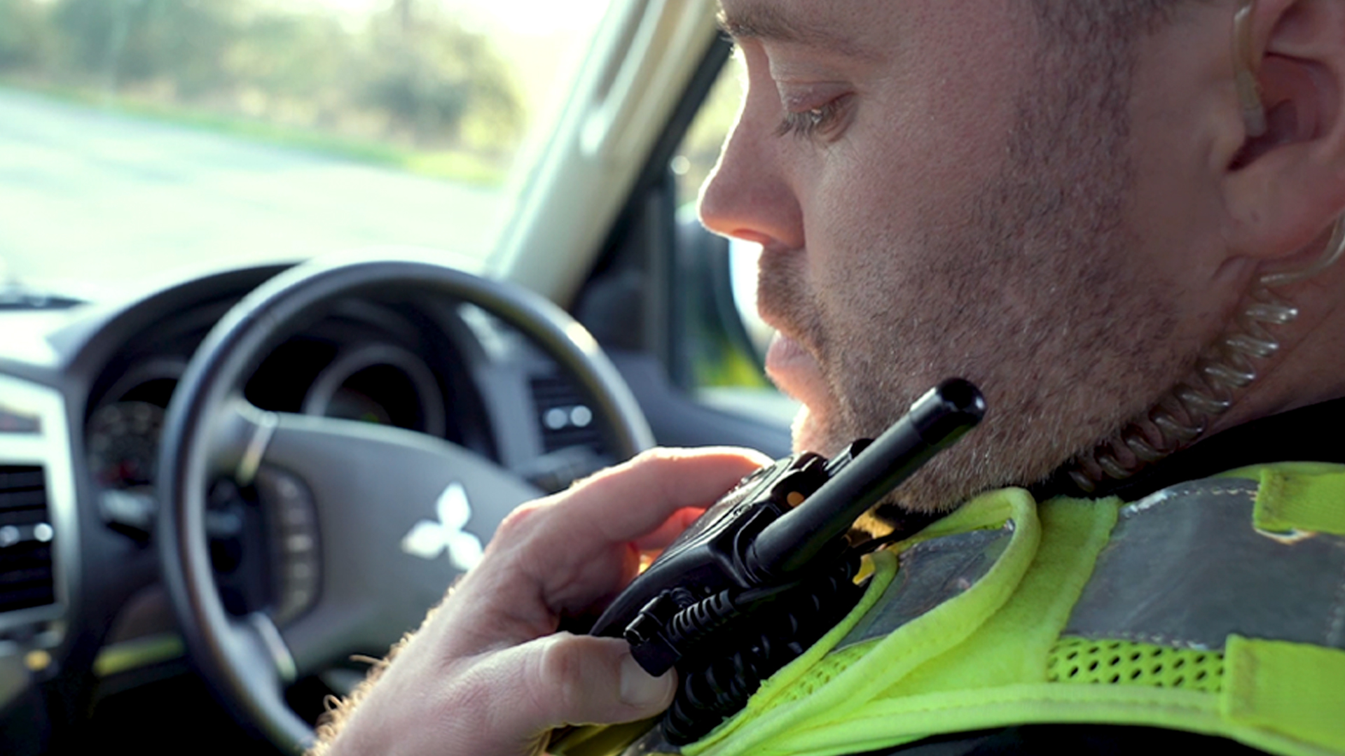 Emergency response officer in car communicating to team through walkie talkie